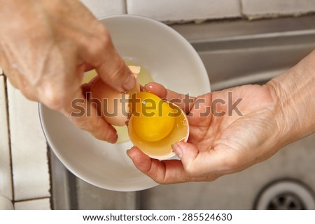 hand separating egg yolk to make bread - stock photo