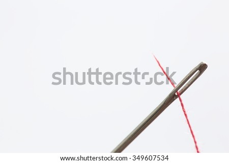 hand sewing needle with red thread bobbin