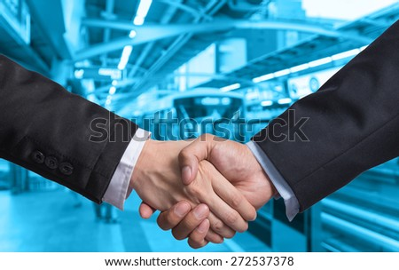 Hand shake between a businessman and a businesswoman on Abstract blurred photo of sky train station with people background - stock photo