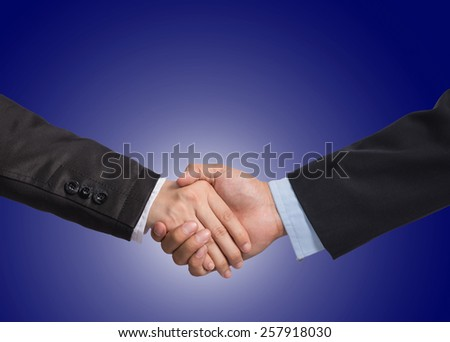Hand shake between a businessman and a businesswoman on dark blue background, include clipping path - stock photo