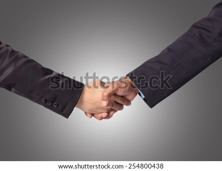 Hand shake between a businessman on gray background - stock photo