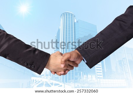 Hand shake between a businessman on Modern business building glass area background - stock photo