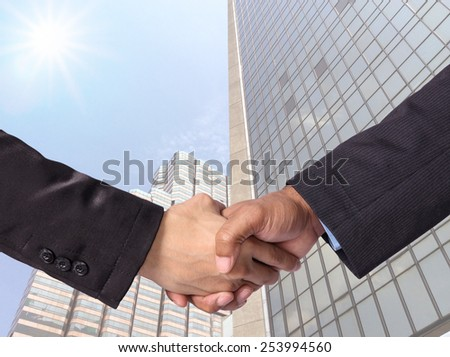 Hand shake between a businessman on Modern glass building background - stock photo