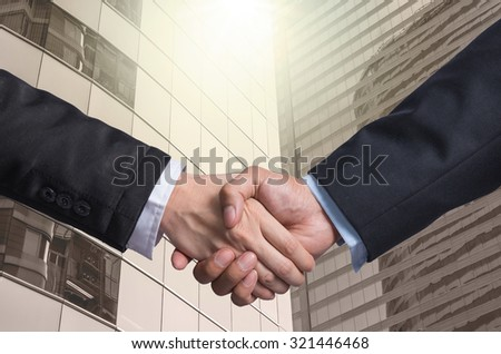 Hand shake between a businessman on Modern glass building background, Business agreement concept - stock photo