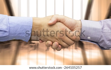 Hand shake in front of wires against room with large window looking on city