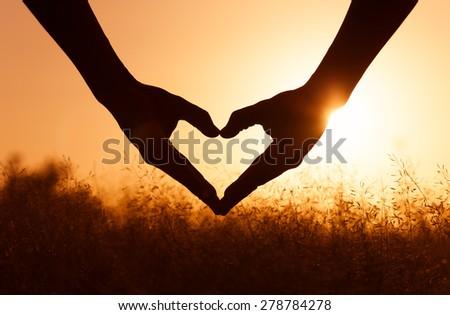 Hand shaped heart at sunset.  - stock photo