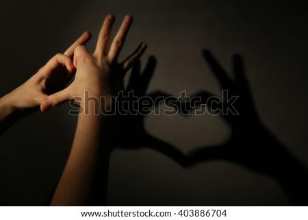 Hand shaped heart on dark background - stock photo