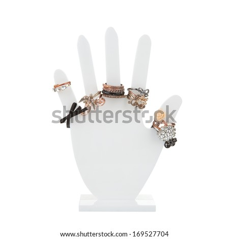Hand-shaped jewelry holder with variety of rings isolated on white - stock photo