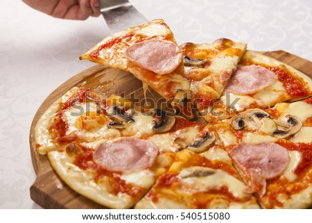 Hand shovel takes a slice of pizza on white background