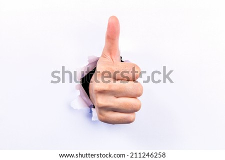 Hand show Thumbs up sign from hole. - stock photo