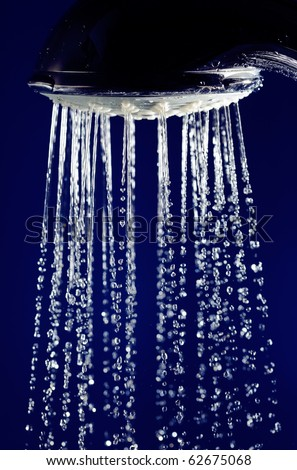 Hand shower douche with stopped motion water drops on deep blue