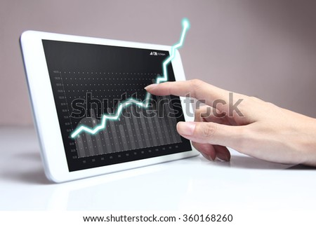 Hand showing a rising graph on tablet, representing business growth.