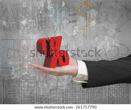 Hand showing businessman hanging on 3D red percentage sign with business concept doodles wall background - stock photo