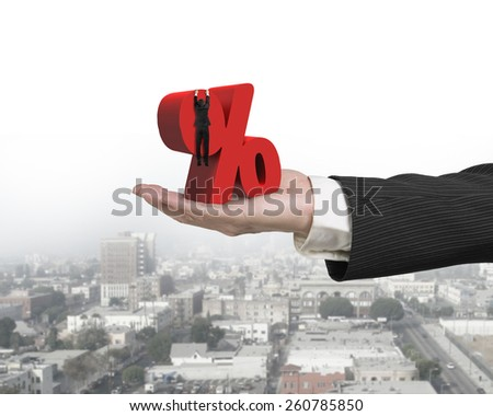 Hand showing businessman hanging on 3D red percentage sign with urban scene background - stock photo