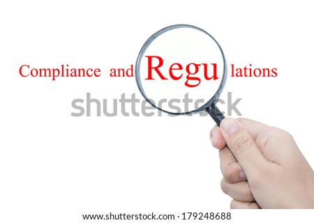 Hand Showing Compliance and Regulations Word Through Magnifying Glass