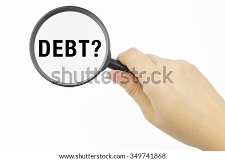 Hand showing DEBT? word through magnifying glass