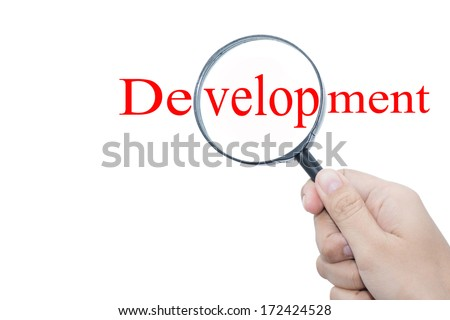 Hand Showing Development Word Through Magnifying Glass  - stock photo