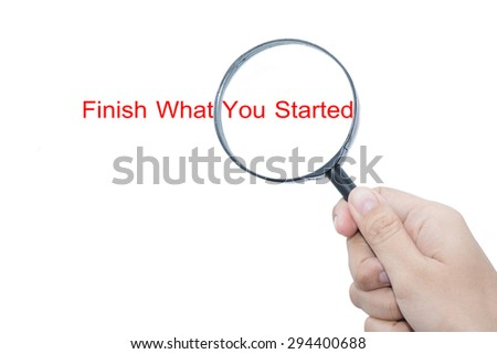 Hand Showing Finish What You Started Word Through Magnifying Glass