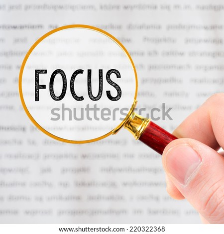 Hand Showing focus Word Through Magnifying Glass - stock photo