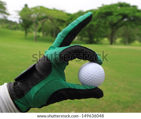 hand showing golf ball over the green grass - stock photo
