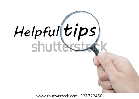 Hand Showing Helpful tips Word Through Magnifying Glass  - stock photo
