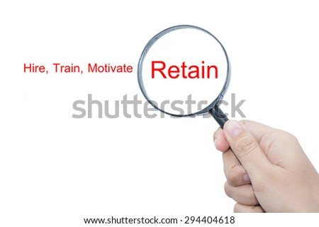 Hand Showing Hire, Train, Motivate , Retain Word Through Magnifying Glass