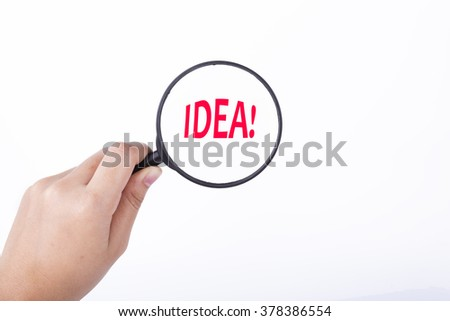 Hand showing IDEA! word through magnifying glass. Isolated white, financial and business concept - stock photo
