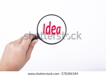 Hand showing IDEA word through magnifying glass. Isolated white, financial and business concept - stock photo