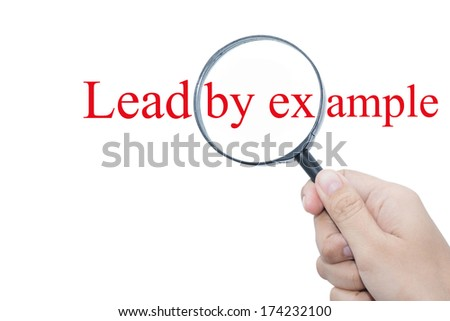 Hand Showing Lead by example Word Through Magnifying Glass  - stock photo