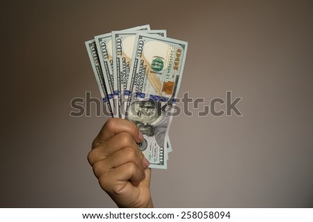 Hand showing notes of one hundred US dollars. - stock photo