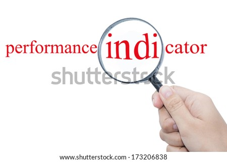 Hand Showing performance indicator Word Through Magnifying Glass  - stock photo