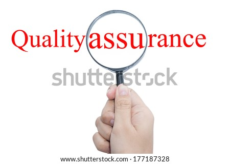 Hand Showing quality assurance Word Through Magnifying Glass  - stock photo