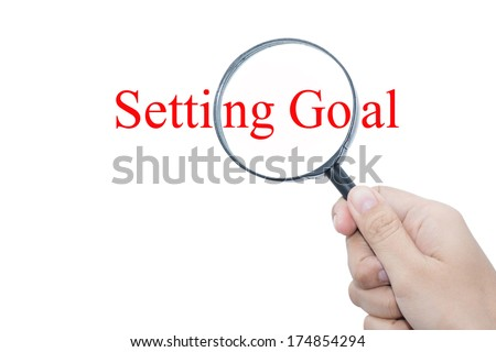 Hand Showing setting goal Word Through Magnifying Glass  - stock photo