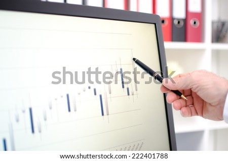 Hand showing stock exchange data graph with a pen on a screen - stock photo