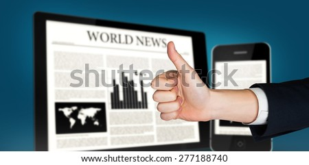Hand showing thumbs up against digital tablet and smartphone showing news - stock photo