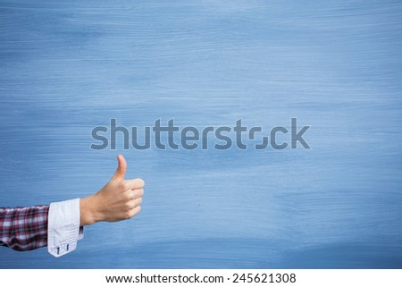 Hand showing thumbs up gesture on blue background - stock photo