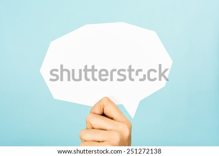 Hand showing white blank speech bubble, straight cutting shape, on blue background. - stock photo