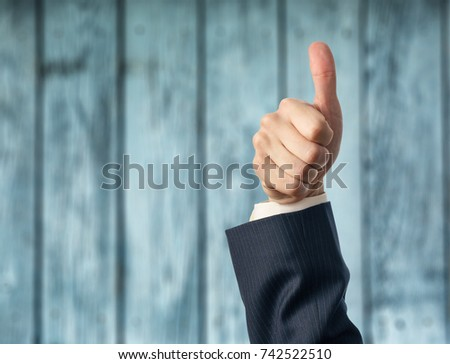 Hand shows thumbs up sign in closeup