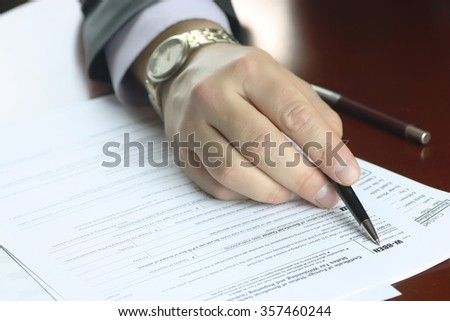 hand signed tax form - stock photo