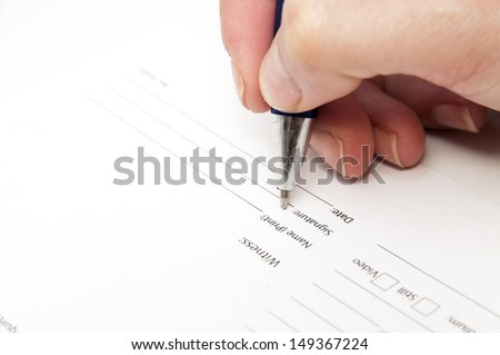 hand signing an agreement on a white background