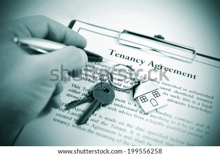 Hand signing tenancy agreement on clipboard with keys and symbolic house keyring - stock photo