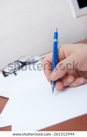 Hand signs the document - stock photo