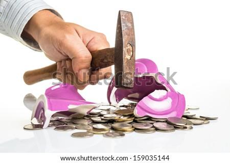 Hand smashing piggy bank with hammer - stock photo