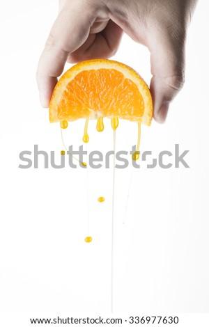 Hand Squeeze Orange Slice With Orange Water Droplets - stock photo