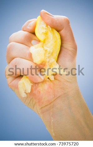 hand squeezing lemon on blue background - stock photo