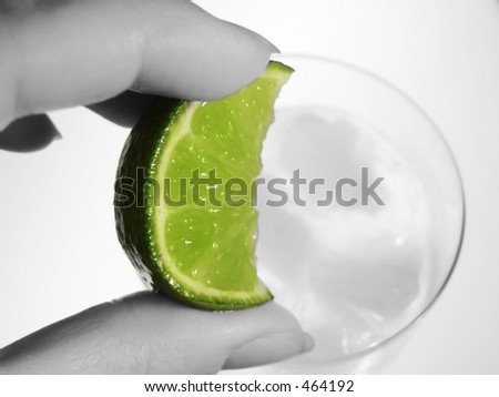 hand squeezing lime wedge into cool drink