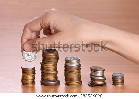 hand stacking coins in piles, closeup