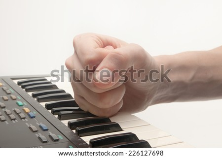 hand striking piano, concept of frustration, music industry, strength and power - stock photo