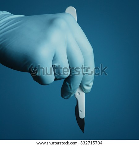 Hand surgeon holding a scalpel - stock photo