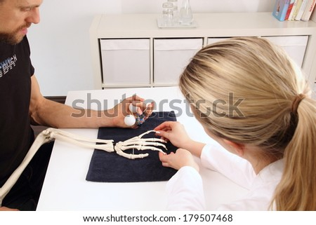 Hand surgeon supports patient with balls - stock photo